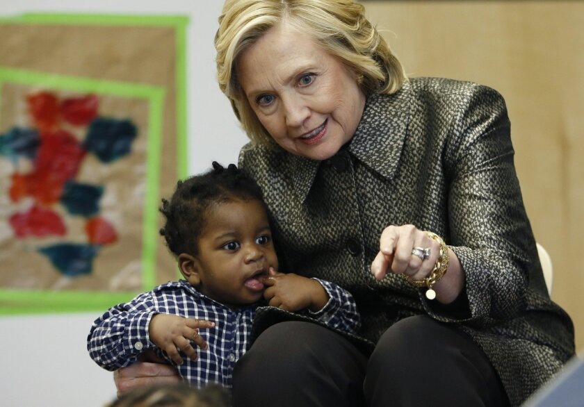 Hillary Rodham Clinton talks to a youngster during a visit to an early childhood development center in the Brooklyn borough of New York, Wednesday, April 1, 2015. Clinton and New York City first lady Chirlane McCray joined forces with the city's deputy mayor in announcing a program to get parents t
