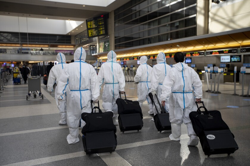 A flight crew wearing personal protective equipment walks through Tom Bradley International Terminal at LAX.