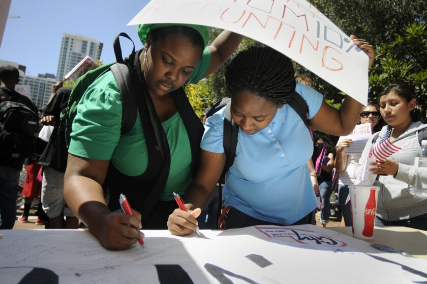 San Diego City College students Alana Moore and Nicole Darden signed a banner protesting budget cuts that have affected their class availability and fees. (David Brooks)