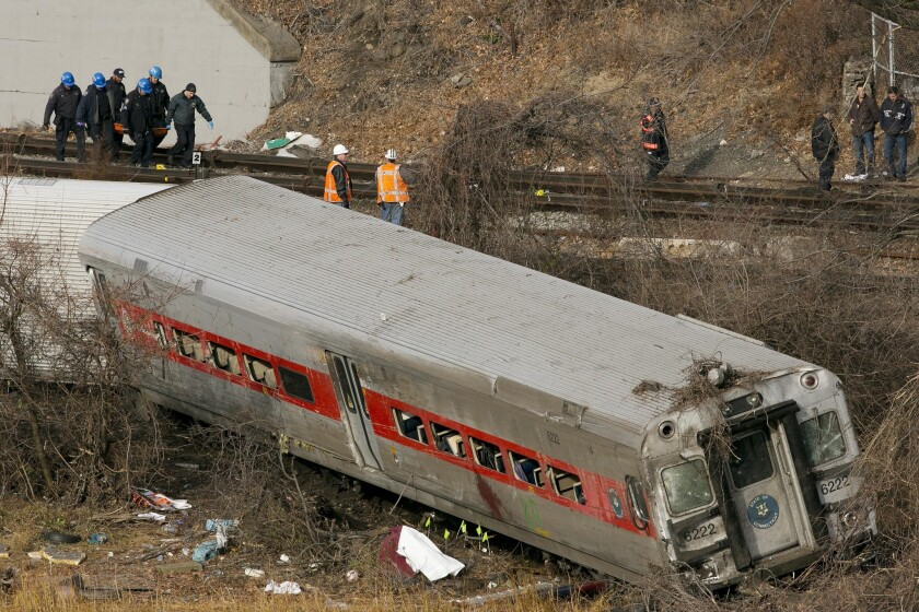 Emergency rescue personnel remove the body of a victim from the site of a train derailment in the Bronx borough of New York.