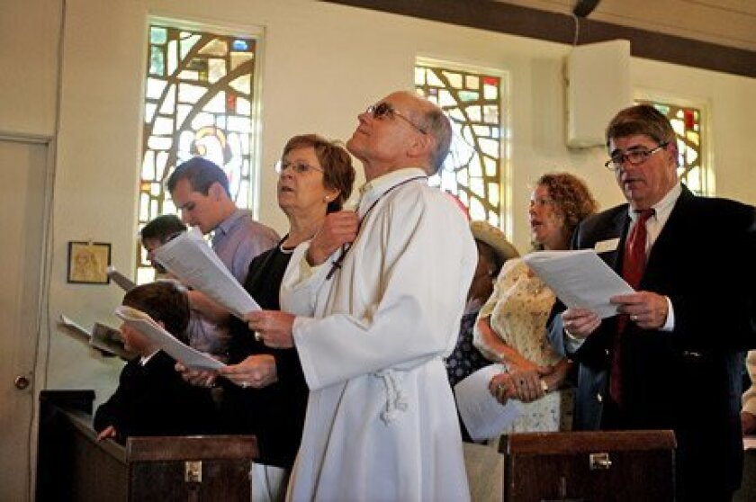 During Easter service yesterday at St. John's Episcopal Church in Fallbrook, David New (left in front row) and family members Marion New and Dale New (with hand over heart) prayed along with Rebecca and Arthur Brown of Fallbrook (second row).  (Laura Embry / Union-Tribune)