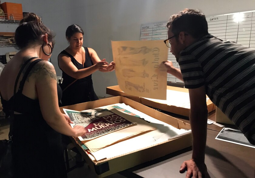 Centro Cultural de la Raza volunteers inspect a box of screen prints from the 1990s stored at the center. Left to right, Alexis Meza, Amelia Enrique and Evan Apodaca.