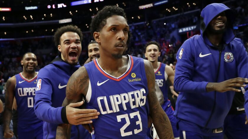 Lou Williams is mobbed by teammates after making the game-winning shot as time expired Sunday against the Brooklyn Nets at Staples Center.
