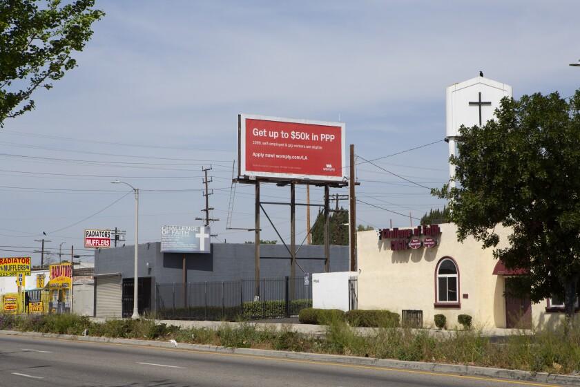 A billboard beside a church advertises PPP loans