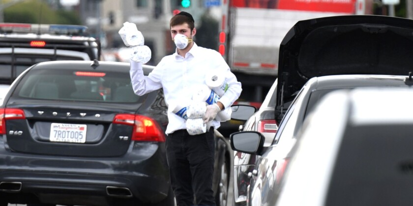 A man in Los Angeles offers free toilet paper and paper towels to motorists Tuesday.