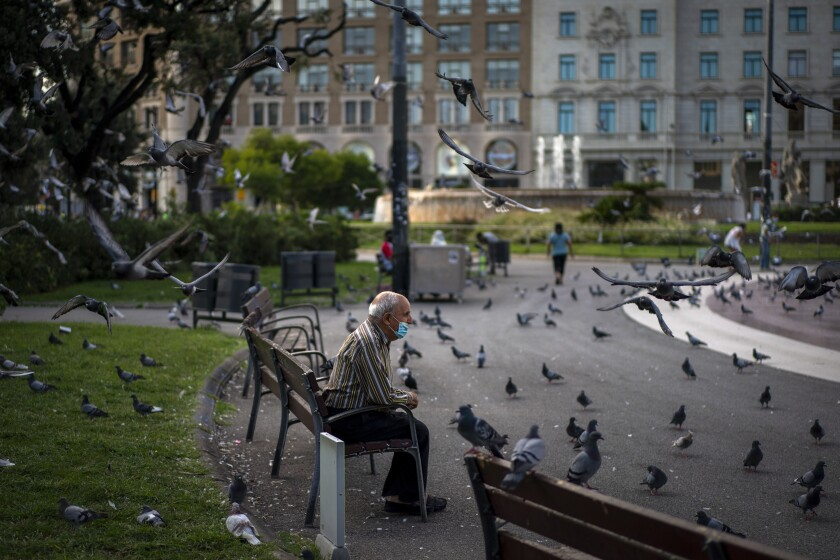 A man wearing a face mask to prevent the spread of coronavirus sits in a square in Barcelona, Spain, Wednesday Sept. 23, 2020. Spain is struggling to contain a second wave of the virus which has killed at least 30,000 people according to the country's health ministry. (AP Photo/Emilio Morenatti)