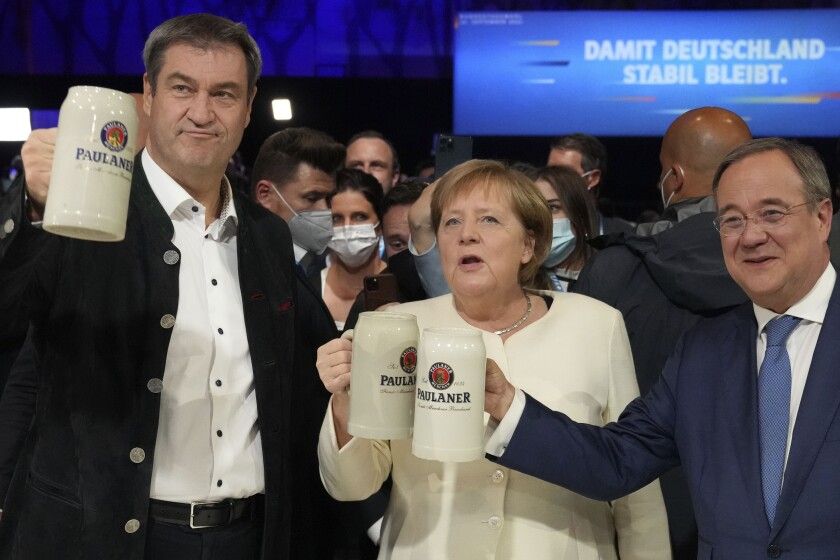 German chancellor Angela Merkel, Bavarian State Governor Markus Soeder, left, and Christian Democrats candidate Armin Laschet attend a state election campaign in Munich, Germany, Friday, Sept. 24, 2021 two days before the General election on Sunday, Sept. 26, 2021. (AP Photo/Matthias Schrader)