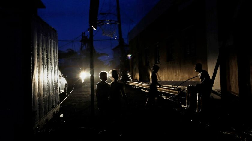 Boys play basketball in near darkness in the La Perla area of San Juan, Puerto Rico, which has no electricity after being battered by Hurricane Maria.