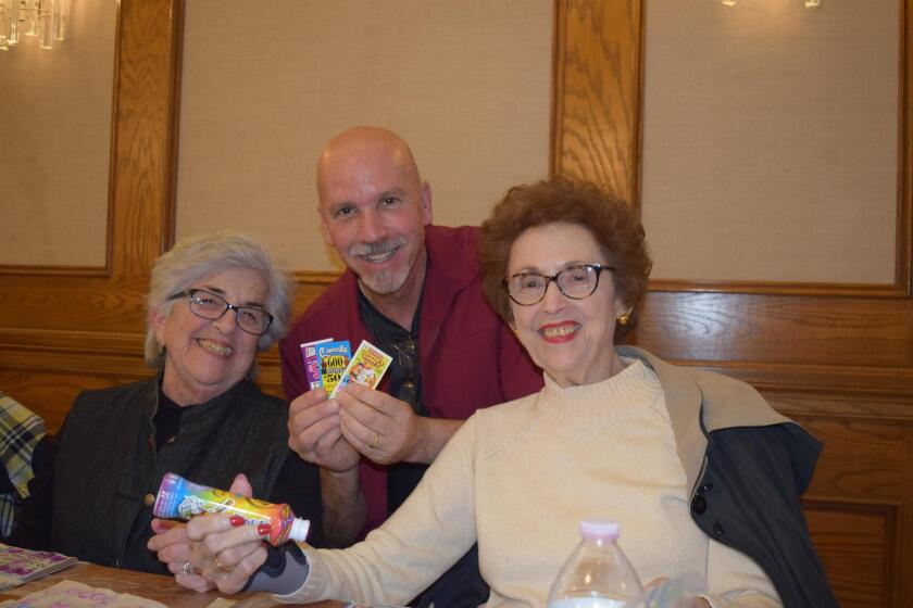 Rodney Guidi (center), chair of the Bingo committee and a volunteer floor worker, poses with regulars Marie Cefalu and Betty Sanfilippo.