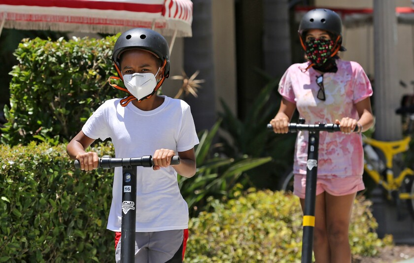 Youngsters on scooters roll down the bike trail near the Balboa Pier while wearing face coverings on Monday.