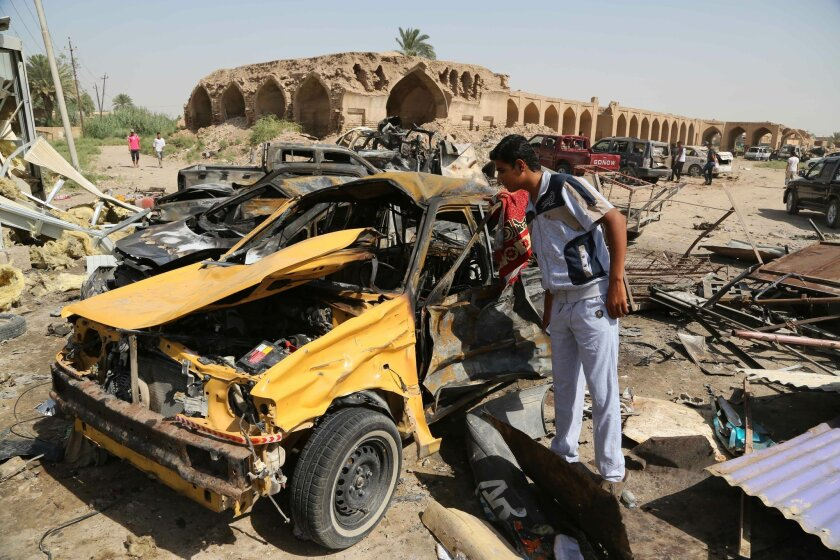 Civilians inspect the aftermath of a suicide car bombing at a busy market in Khan Bani Saad in the Diyala province, about 20 miles (30 kilometers) northeast of Baghdad, Iraq, Saturday, July 18, 2015. A suicide car bombing in Iraq's eastern Diyala province killed at least 80 people gathered at a marketplace to mark the end of the holy month of Ramadan on Friday. (AP Photo/Karim Kadim)