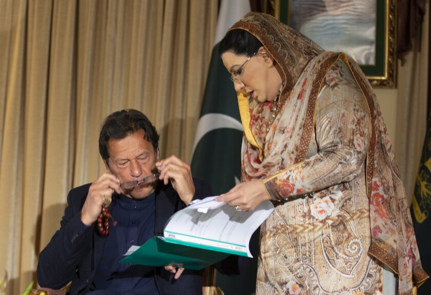 Pakistan government spokesperson Firdous Ashiq Awan consults with Pakistani Prime Minister Imran Khan in Islamabad, Pakistan, Monday, March 16, 2020. Khan said Monday he fears the new coronavirus will devastate developing nations' economies, and warned richer economies to prepare to write off the debts of the world's poorer countries. In an interview with The Associated Press he also called for an end to sanctions on Iran saying they were crippling the poor nation's ability to even contain the spread of the coronavirus. For most people, the new coronavirus causes only mild or moderate symptoms. For some it can cause more severe illness. (AP Photo/B.K. Bangash)