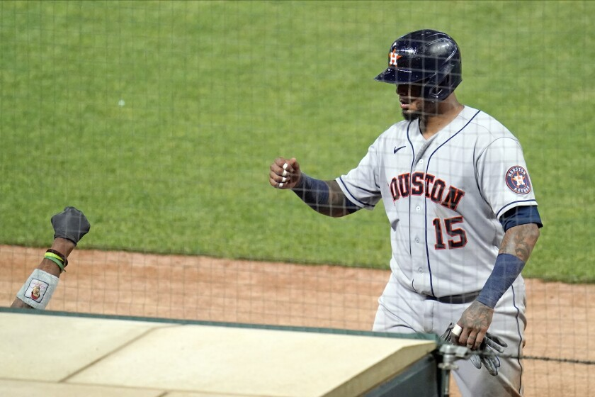 Houston Astros' Martin Maldonado (15) has a waiting fist-bump as he scores on a single by Michael Brantley in the ninth inning of a baseball game against the Minnesota Twins, Friday, June 11, 2021, in Minneapolis. (AP Photo/Jim Mone)