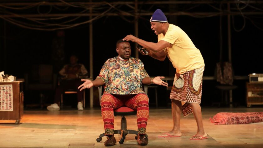 "Ekow Quartey, seated, and Patrice Naiambana in ""The Barber Shop Chronicles,"" playing at the Freud Playhouse at UCLA. The play is an import from England about African immigrants bonding at barbershops in London and Africa."