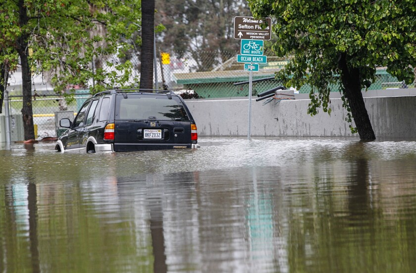 A car sits in area flooded by heavy rain and the rising San Diego River in Mission Valley last April.