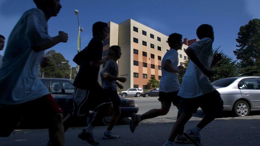 A group of athletes runs past Mary Park Hall at San Francisco State University.