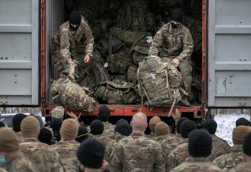 U.S. Army soldiers wait as their duffels are unloaded from a truck upon their return to Ft. Drum, N.Y., from Afghanistan.