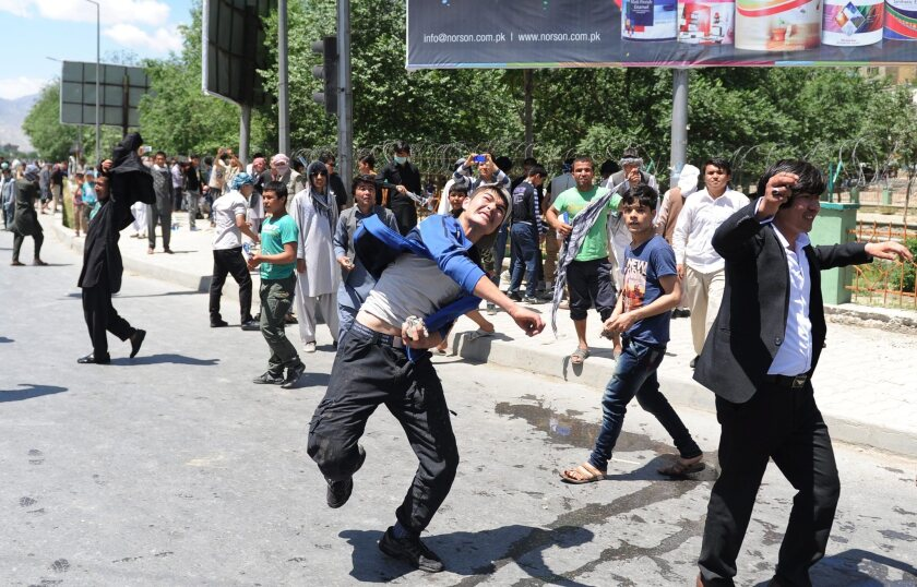 Afghan protesters from the Hazara minority clash with riot police in Kabul, Afghanistan, on Monday. They were protesting the controversial rerouting of a new power line.