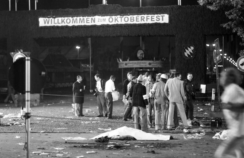 ARCHIVO - La foto de archivo del 26 de septiembre de 1980 muestra una víctima tendida cerca del cartel de bienvenida a la Oktoberfest, la fiesta de la cerveza, en Múnich, Alemania. Una bomba dejó 13 muertos y más de 200 heridos en un ataque de la extrema derecha. (AP Foto/Dieter Endlicher, FILE)