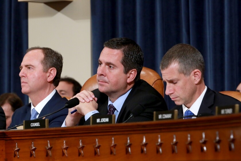Rep. Adam Schiff, left, Rep. Devin Nunes and Republican counsel Steve Castor list to testimony during an open hearing of the House Intelligence Committee in the impeachment inquiry of President Trump.