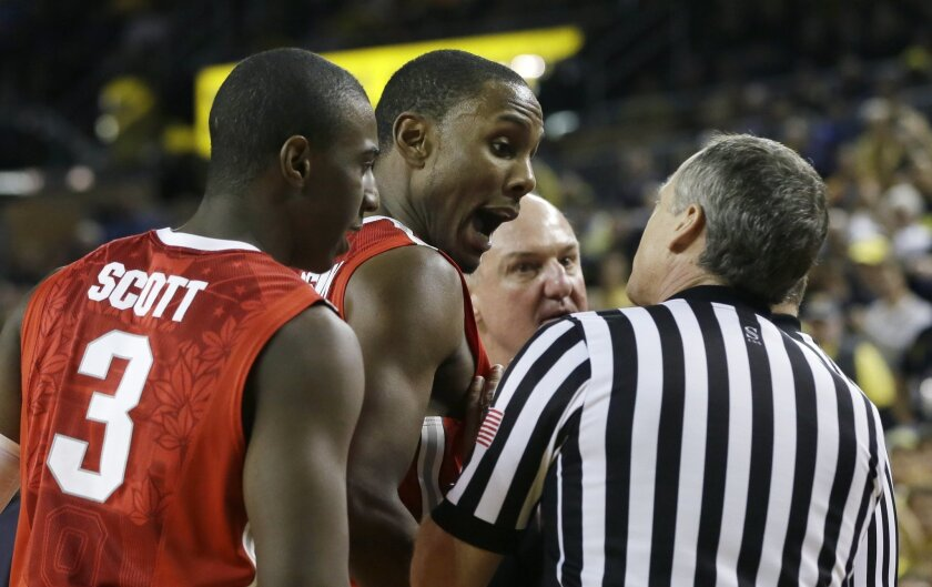 Ohio State forward Sam Thompson, center, talks with a referee during the second half of an NCAA college basketball game against Michigan, Sunday, Feb. 22, 2015, in Ann Arbor, Mich. Michigan defeated Ohio State 64-57. (AP Photo/Carlos Osorio)