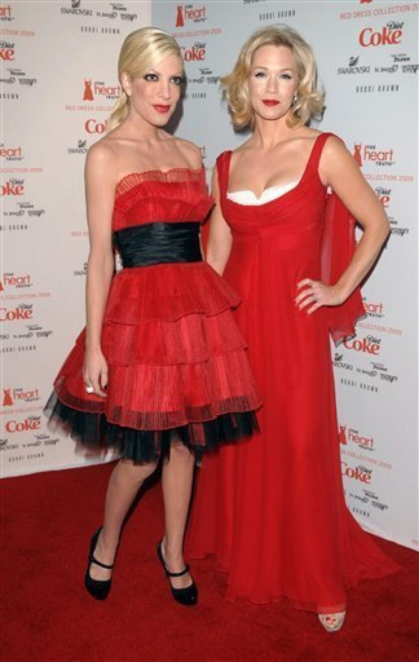 Actors Tori Spelling, left, and Jennie Garth arrive to the Heart Truth's Red Dress collection during Fashion Week in New York on Friday, Feb. 13, 2009. (AP Photo/Peter Kramer)