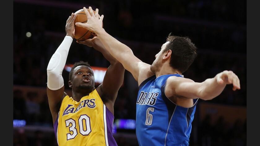 Lakers forward Julius Randle, shooting over Dallas Mavericks center Andrew Bogut, has two triple-doubles this season and three in two full seasons.