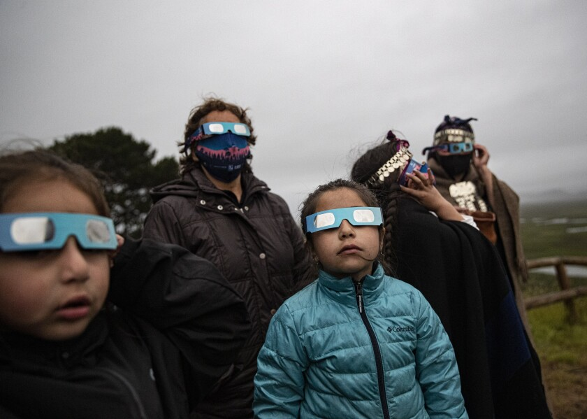 A Mapuche Indigenous family uses special glasses to try and observe a total solar eclipse in Carahue, La Araucania, Chile, Monday, Dec. 14, 2020. The total eclipse was not visible from Carahue because of an overcast sky. (AP Photo/Esteban Felix)