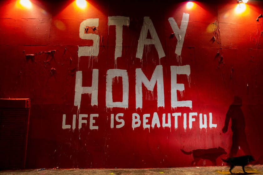 "A man walks by a mural that says ""Stay Home, Life is Beautiful."""