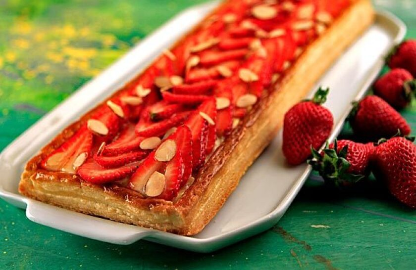 Fresh berry tart has a bed of custard between the flaky puff pastry and the berries.