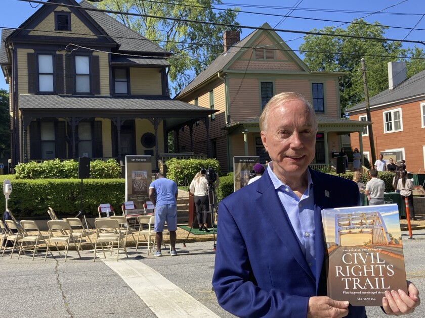 """Lee Sentell, author of """"The Official United States Civil Rights Trail"""" companion book, poses with the book outside the birth home of the Rev. Martin Luther King Jr. in Atlanta on Wednesday, June 23, 2021. The U.S. Civil Rights Trail includes more than 120 sites — churches, schools, courthouses, museums — across 15 states, mostly in the South. The new companion book includes more than 200 images of those landmarks today, as well as photographs from the civil rights era. (AP Photo/Kate Brumback)"""