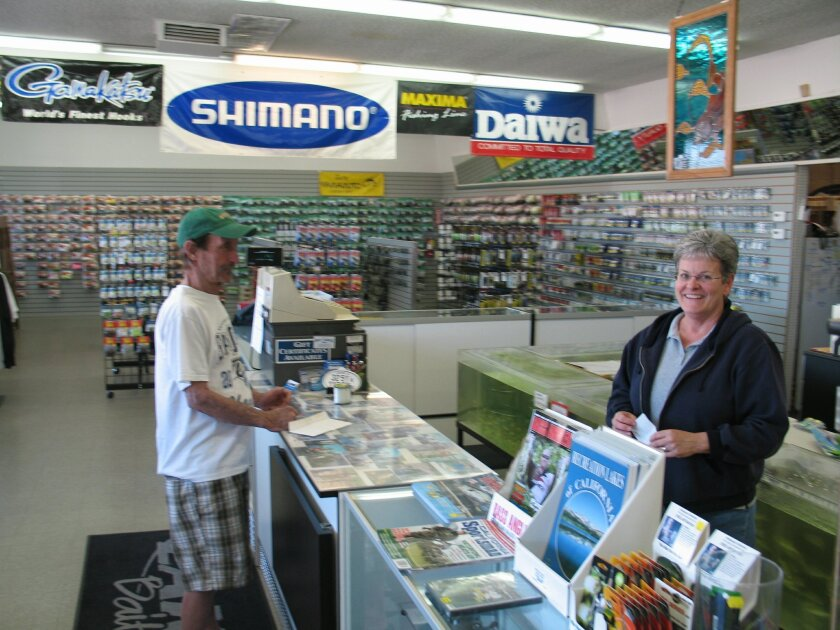 Diane Vance, owner of Lakeside Bait and Tackle, attends to angler and customer Terry Stratton, who was stocking up for trips to Lake Wohlford and San Diego Bay.