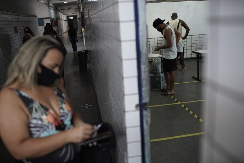 Personas sufragan en un centro de votación el domingo 29 de noviembre de 2020 durante la segunda ronda de las elecciones municipales, en Río de Janeiro, Brasil. (AP Foto/Silvia Izquierdo)