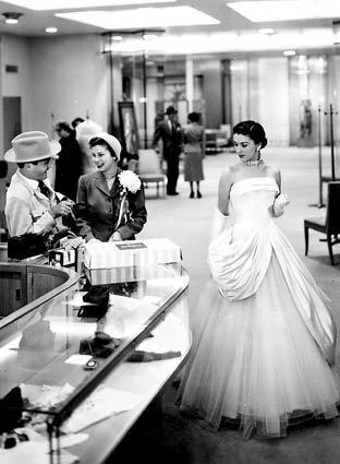 "A live ""mannequin"" models a gown while shoppers enjoy themselves at the Neiman Marcus store in downtown Dallas."