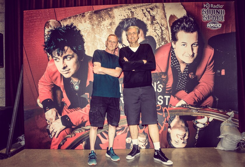 "Kevin Ryder, left, and Gene ""Bean"" Baxter against a Green Day backdrop"