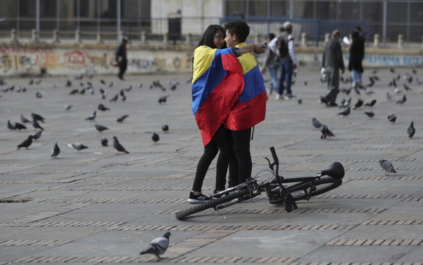 Two people wrapped in a large Colombian flag