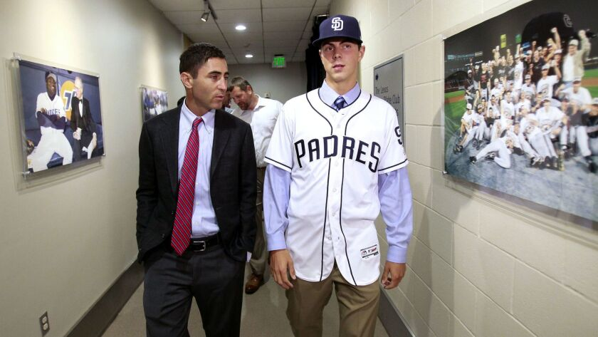 Padres first-round selection left handed pitcher MacKenzie Gore, right, walks with Padres General Manager A.J. Preller through a hallway as they make their way to the field at Petco Park on Saturday, June 24, 2017.