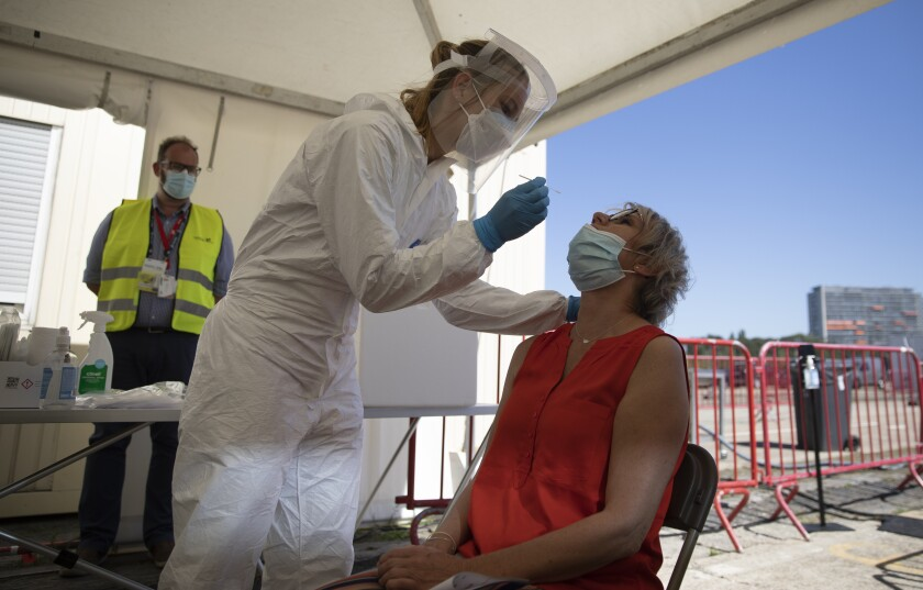 FILE - In this Wednesday, Aug. 5, 2020 file photo, healthcare workers perform tests in a tent at a drive-thru COVID-19 testing site in Antwerp, Belgium. With nothing on their agendas for months to come, organizers of music festivals in Belgium want to use their know-how to help the coronavirus vaccination campaign. The Belgian government has set up the goal to vaccine about 70 percent of the country's population, the equivalent of eight million people, when efficient COVID-19 shots become available. (AP Photo/Virginia Mayo, File)