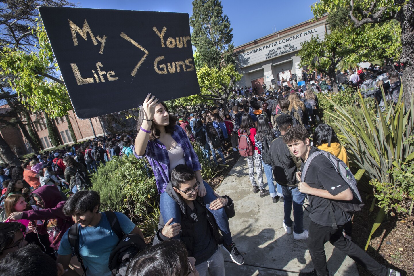 Hamilton High student Sofia Mosqueda, 15, holds a sign while sitting on the shoulders of friend, Christopher Cetrulo,16, during walkout in support of Parkland shooting victims on National Walkout Day in Los Angeles.