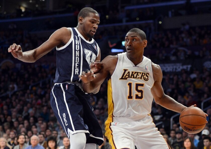 Metta World Peace dribbles as he is guarded by Kevin Durant of the Oklahoma City Thunder.