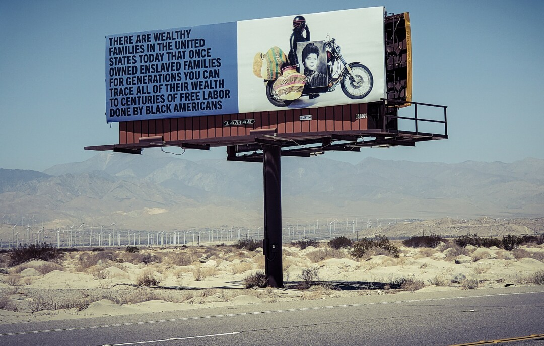 """A billboard of a motorcycle and old photo links some of today's wealth to """"centuries of free labor done by Black Americans."""""""