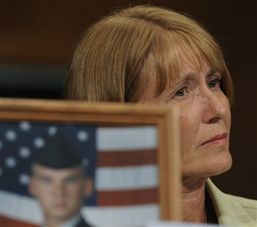 In this July 11, 2008 file photo, Larraine McGee of Huntsville, Texas, with a photo of her son, Staff Sgt. Christopher Everett in the foreground, listens as she prepares to testify on Capitol Hill in Washington. (AP Photo/Susan Walsh)