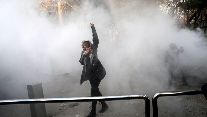A university student attends a protest at Tehran University while a smoke grenade is thrown by anti-riot police on Dec. 30, 2017, in a photo obtained by the AP outside Iran.