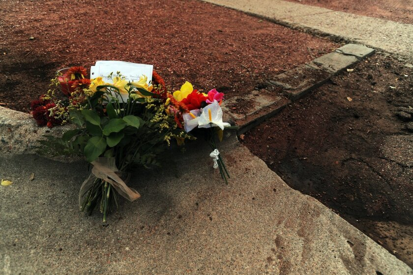 Flowers mark the spot Sunday, Nov. 1, 2015, where an unidentified man was killed during Saturday's shooting spree in Colorado Springs, Colo. (Daniel Owen/The Gazette via AP)