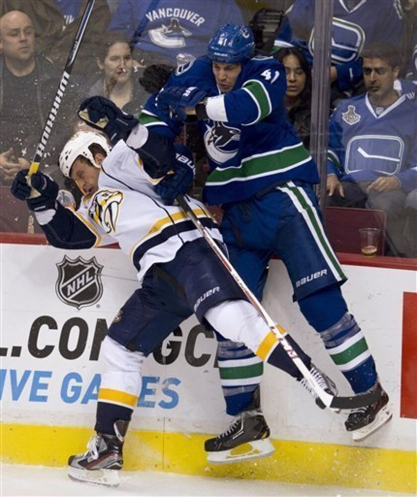 Vancouver Canucks defenseman Andrew Alberts (41) goes into the boards with Nashville Predators left wing Richard Clune (16) during the third period of their NHL hockey game, Thursday, March,14, 2013, in Vancouver. (AP Photo/The Canadian Press, Jonathan Hayward)