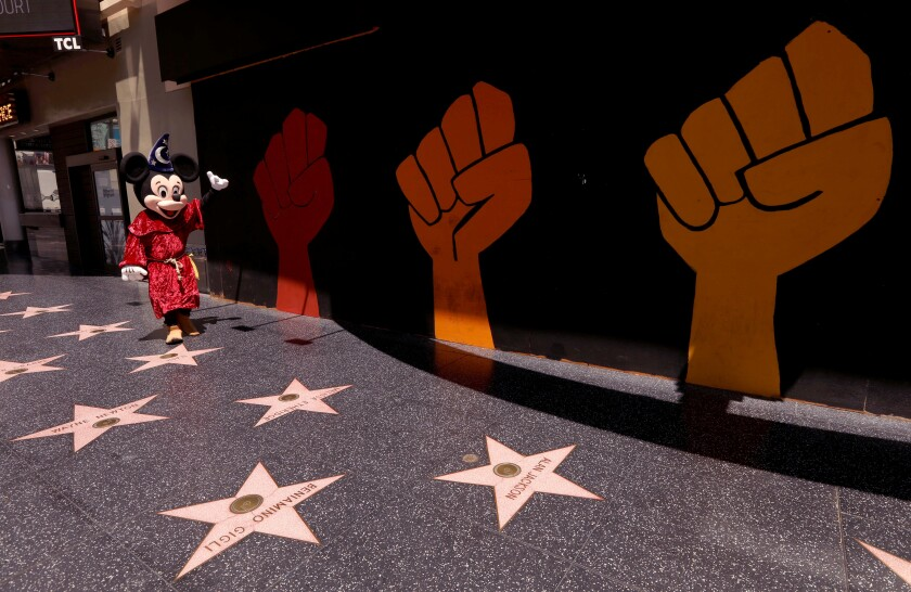 Street performer Javie Rubio, dressed as Mickey Mouse, looks for customers to pose for photos on the empty Walk of Fame.