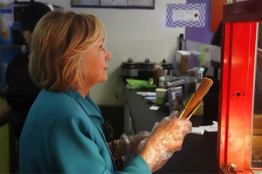 La exsecretaria de Estado y excandidata presidencial estadounidense Hilary Clinton sostiene un churro durante una visita a una iniciativa de la Fundación para Puerto Rico, en Humacao (Puerto Rico). EFE/Archivo