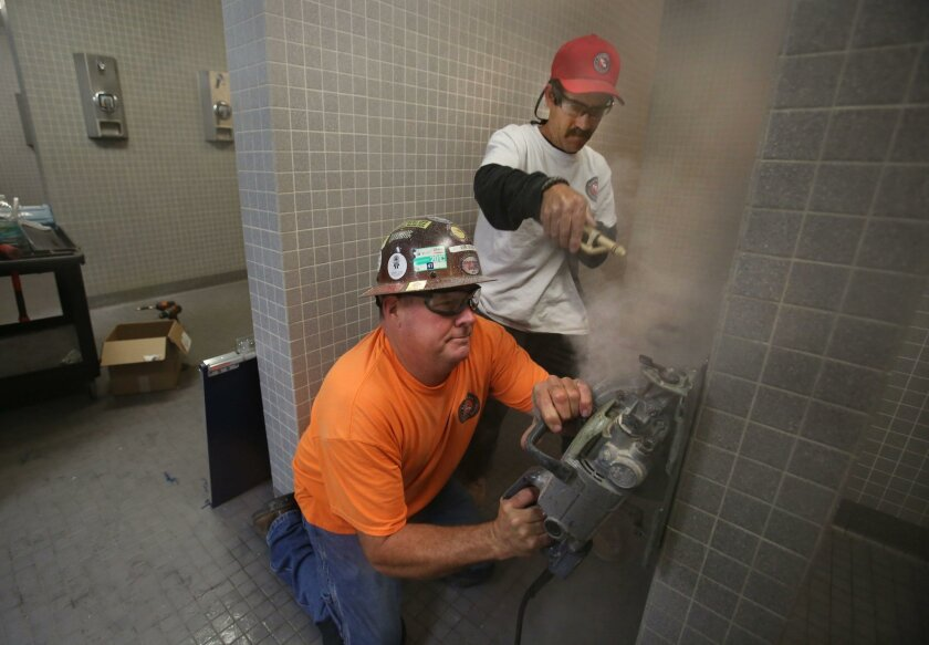 Eric Dunn cuts the tile on a shower wall while Todd Miehls sprays water to keep the concrete dust down. They were preparing the wall for a privacy door in the shower area of the women's locker room  at Rancho Bernardo High to accommodate transgender students. |