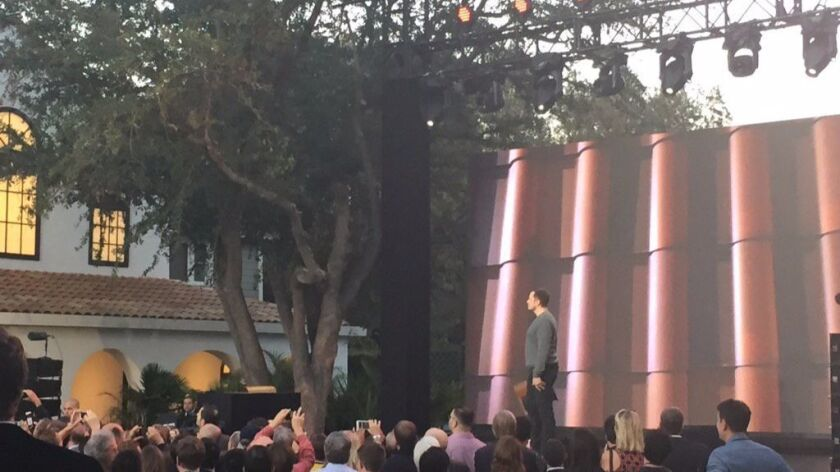 """At Universal Studios Hollywood's old """"Desperate Housewives"""" set, Tesla CEO Elon Musk shows off a new solar tile roof to be produced by SolarCity, which Tesla is buying. Four Wisteria Lane homes on the set were re-roofed with the tiles."""