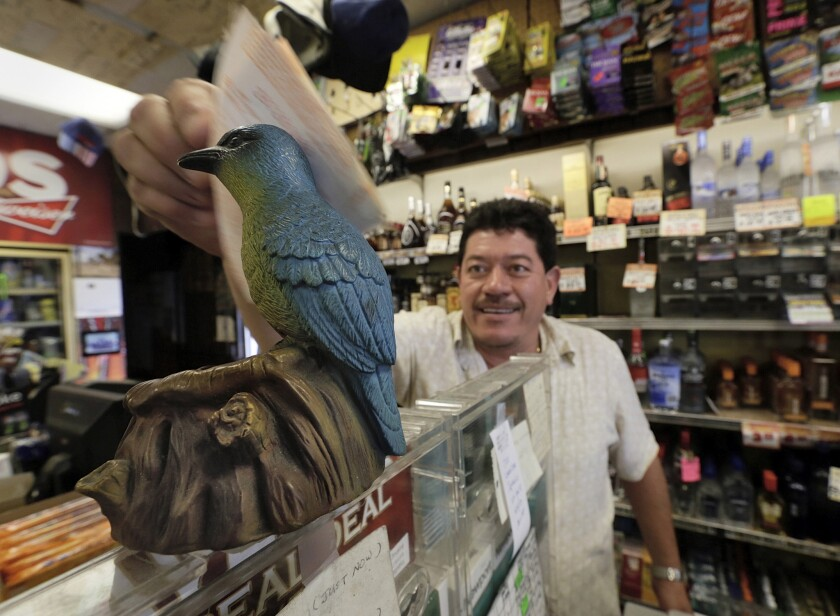 Ronald Marin rubs his lottery tickets on the wings of a bluebird statue for good luck at Bluebird Liquor in Hawthorne on Thursday. The jackpot for the multstate game has soared to $550 million.